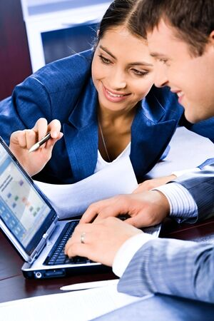 explaining: Business woman pointing at laptop and explaining a plan of work to colleague  Stock Photo