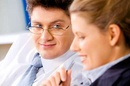 Image of business man with glasses gazing at his colleague while discussing their work   photo