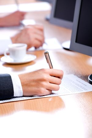 Vertical image of hand holding a pen in a working environment photo