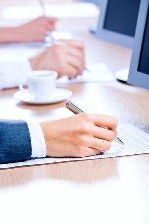 cuadro sinoptico: Close-up de manos de la gente de negocios a tomar notas en los documentos de Foto de archivo