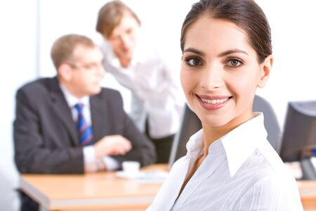Face of beautiful employee with brown eyes on the background of her colleagues Stock Photo - 2506979