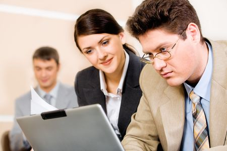 Successful business man and woman looking at the laptop in a working environment photo