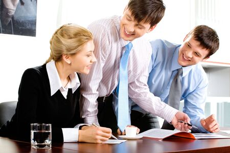 Three business people gathered together around the table discussing important questions Stock Photo - 2507055