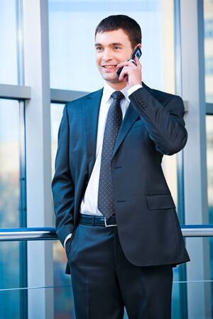 Portrait of confident business man calling on the mobile in the office  photo