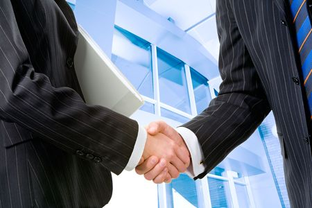 great deal: Two partners shaking hands at meeting in front of building