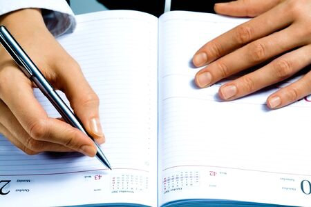 Image of writing instrument in human hands over notepad  photo