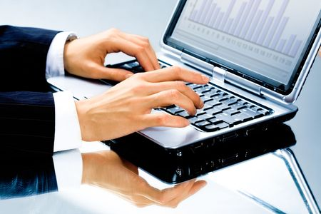 Image of human hand typing a business document on the laptop photo