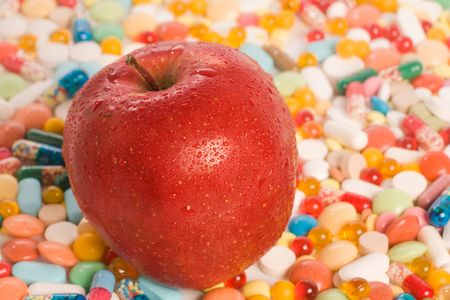 depressant: Conceptual photo of red apple with tablets on a background  Stock Photo