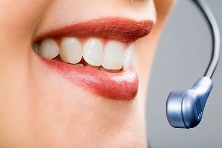 Close-up of smiling woman's mouth and teeth with microphone Stock Photo - 2529497