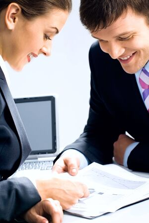 Two business people looking at business-plan and discussing it photo