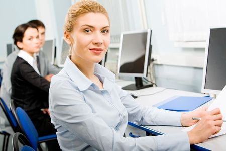 Confident business lady sitting by the computer in the office on the background of her two partners Stock Photo - 2529500