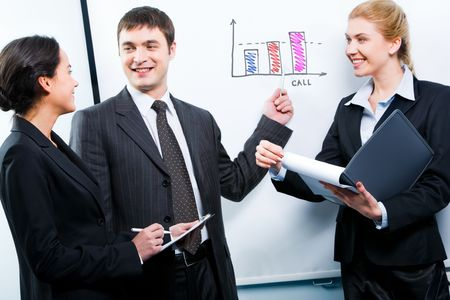 Portrait of confident man showing a plan to business partners  photo
