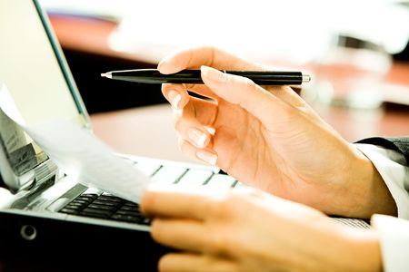 hand with pen: Close-up of businesswoman�s hands holding a pen and a document over the laptop in the office