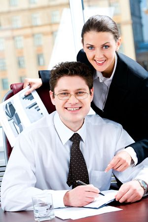 Portrait of two business partners looking at camera with happy smiles in an office on the background of window photo