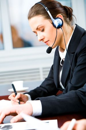 Portrait of telephone operator with headset writing something in the office  photo