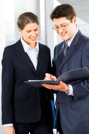 Portrait of two business people standing in the office looking into folder with business plan with smiles photo
