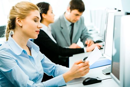 Closeup of confident student sitting at the desk holding a paper and a pen and looking into the document in the computer classroom on the background of two more students Stock Photo - 2576323
