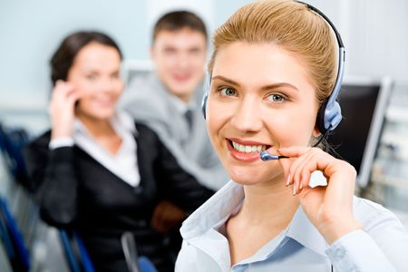 Closeup of smiling beautiful business woman with headset on the background of her business partners Stock Photo - 2553143