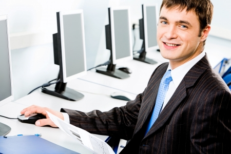 Portrait of handsome business man sitting at the table and touching a computer mouse in the classroom Stock Photo - 2553698