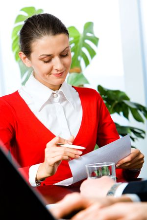 Portrait of pretty woman reading a document in the office Stock Photo - 2567159