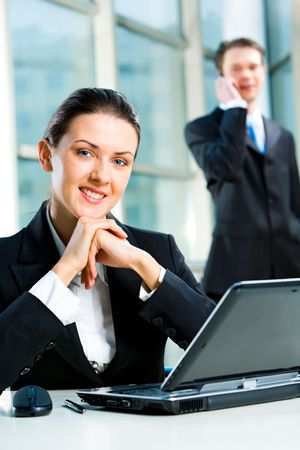 Portrait of beautiful secretary sitting at the table on the background of business man  Stock Photo - 2567194