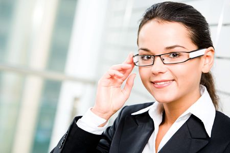 Self-confident woman in suit touching her glasses photo