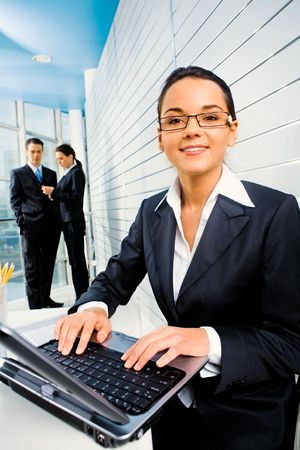 Successful woman doing some computer work on the background of business people in the office  photo