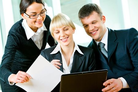 Group of three business people looking at monitor of laptop photo