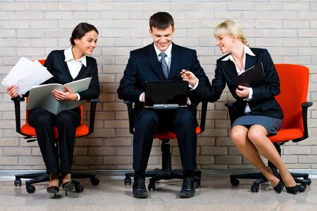 Image of business people sitting on the red armchairs and working on the background of brick wall   Stock Photo - 2568327