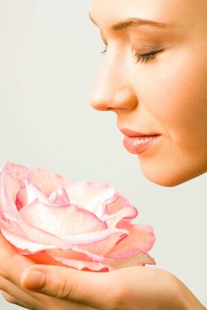 Young pretty woman enjoys a smell of a pink rose photo