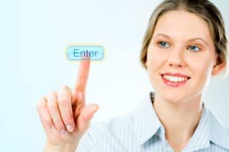 Portrait of businesswoman looking at the enter button and touching it with her forefinger with smile photo