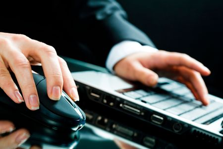 Image of human hands working on the laptop and computer mouse Stock Photo - 2602351