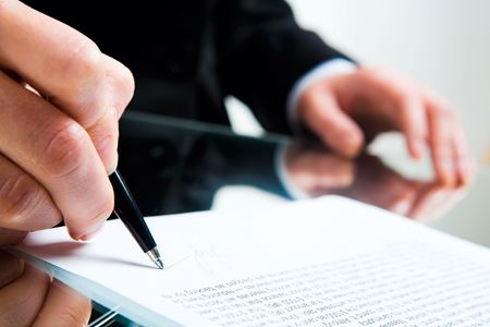 Closeup of business ladys hand with pen signing a contract on the background of her other hand touching the table