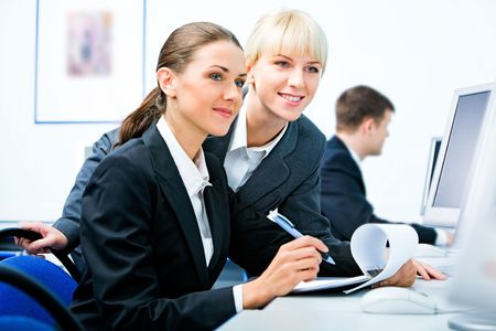 Portrait of two business ladies sitting in the computer room and looking into the computer screen at the background of working businessman photo