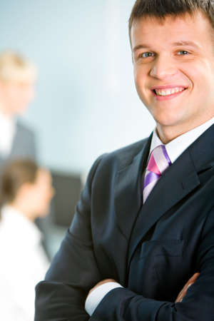 folding arms: Portrait of a smiling handsome man folding his arms on the background of two business ladies