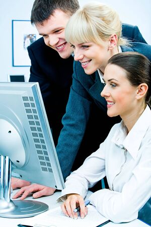 Image of three business people looking at the computer screen with smiles Stock Photo - 2602237