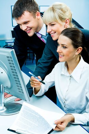 Businessteam of three smiling people looking at the monitor in the computer room photo
