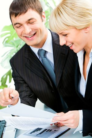 Vertical image of two smiling business colleagues discussing business documents in the office photo