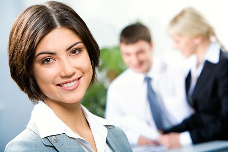 friendly people: Face of beautiful woman on the background of business people