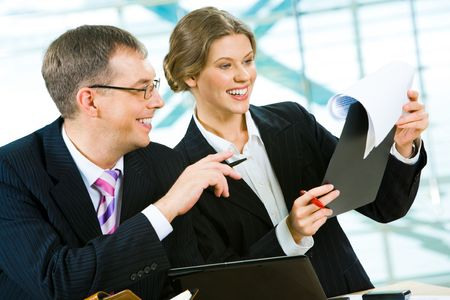 Portrait of two smiling businesspeople doing together some paperwork in at the table the office  photo