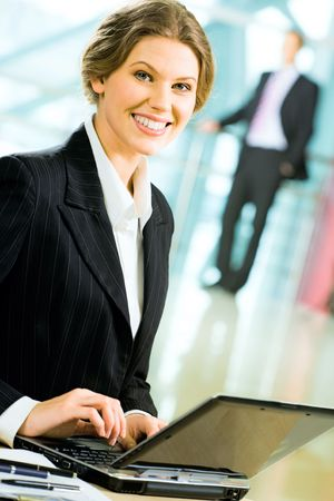 Portrait of smiling businesswoman sitting in the office and typing on the laptop at the background of standing businessman photo