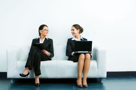 Image of two businesswomen wearing suits sitting on the white sofa smiling at each other on the background of wall photo