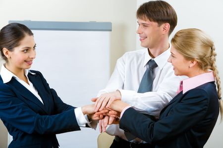 Portrait of three smiling business partners with a pile of their hands and looking at each other on the background of whiteboard in the office Stock Photo - 2634725