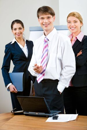 Group of three business people looking at camera and standing in the office photo