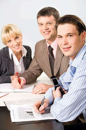 Portrait of three confident people sitting at the table Stock Photo - 2634751