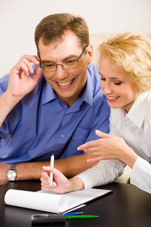Photo of young woman and smiling man discussing a working project at meeting Stock Photo - 2641015