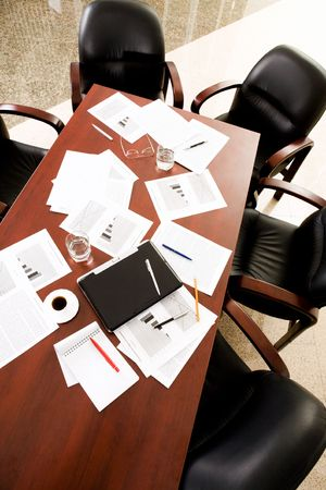 Empty boardroom: black chairs around table with business objects on it  Stock Photo