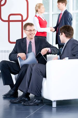 two people with others: Two businessmen are negotiating on the background of people shaking each others hands