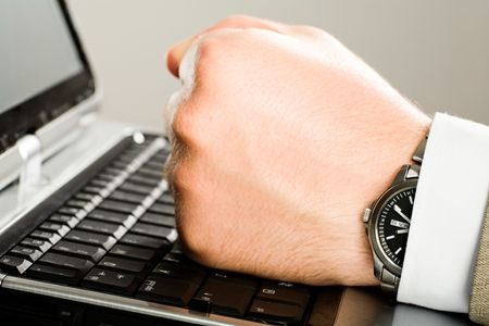 masculin: Image of human  fist on the keyboard of laptop