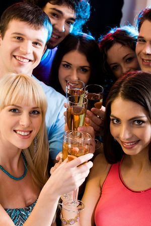 Image of smiling friends holding alcoholic drinks and looking at camera photo